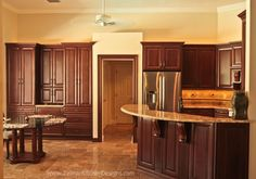 Stunning Cherry Kitchen Cabinets in Traditional Home. Dark cabinetry with french pattern travertine floors. DREAM KITCHEN!  Visit https://www.zelmarkitchendesigns.com for more design ideas.