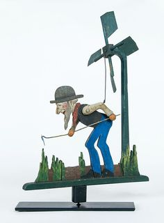 WHIRLIGIG OF FARMER  Farmer with a hoe, articulated arms, white bearded man with brown derby hat, red scarf and black vest, mounted on metal base, 24 h, 16 l.