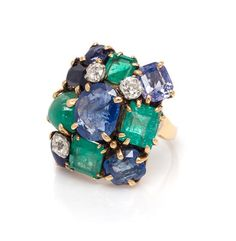A Yellow Gold, Sapphire, Emerald and Diamond Ring, Seaman Schepps,  containing one oval mixed cut sapphire measuring approximately 11.17 x 9.05 x 4.50 mm, three oval and cushion cut sapphires, two oval cabochon cut star sapphires, three octagonal step cut emeralds, one oval cabochon cut emerald, and three old mine cut diamonds weighing approximately 0.75 carat total