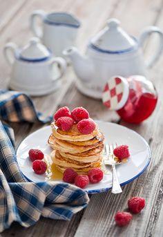 Mini pancakes with raspberries .