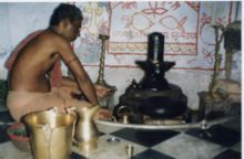 Hindu priest in ritual worship of Shiva in the form lingkam . The lingkam black object is shown to the right