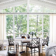 Take Advantage of the View  If you want to highlight the view outside of your dining space, keep your furnishings and accessories simple. This dining table is centered in front of a large back wall of windows, and the space is softened with simple curtains.