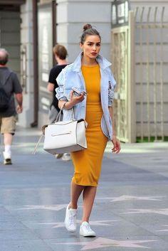 Como usar amarelo em diversos looks: guia completo. Olivia Culpo, jaqueta jeans, vestido de comprimento midi, tênis branco