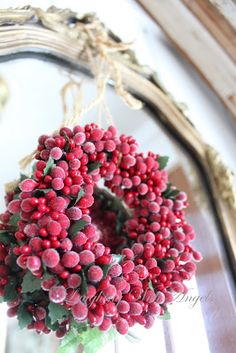 Frame or mirror with frosty red berry wreath... front door or entryway...