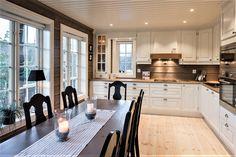 Klassisk kjøkken malt i heldekkende bomull med brunoljet eikeplate og skålhåndtak i antikk tinn. Kjøkkenet er takhøyt og har heltre eikestokk i ventilatorhetten.