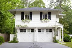 Gorgeous home exterior boasts a traditional two car garage framed by white siding and positioned under an above-garage apartment with two windows flanked by black shutters and fitted with white flower boxes. Above Garage Apartment, Garage Apartment Plans, Garage Apartments, Garage Apartment Interior, Carriage House Apartments, White Apartment, Apartment Door, White Siding, Black Shutters