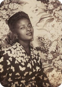 Beautiful  woman . With this hairs style, and flowered dress and background, she looks like Frida.    1940