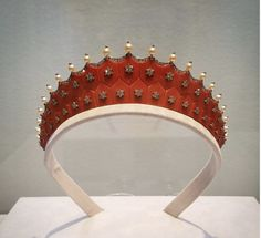 CARTIER ART DECO CORAL TIARA ~ Designed as two rows of graduating coral tablets, each tablet centers upon a diamond star motif and is topped with graduating pearls and collet-set diamonds, flanked on each side by single and old-cut diamond festoons. Its estimate is $200,000 - 300,000,