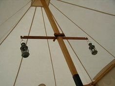 """A way to hang things from the center post without drilling: """"Two wooden bolts pass through the long cross bar and screw into the wooden nut. The nut has a slot just wide enough for the center pole to keep the whole thing from tilting."""""""