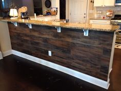 Peel and stick wood flooring underneath a kitchen bar! Total cost was $47!!