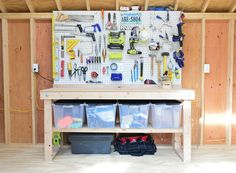Workbench with pegboards for garage or workroom or shed organization! So much function is crammed in here.