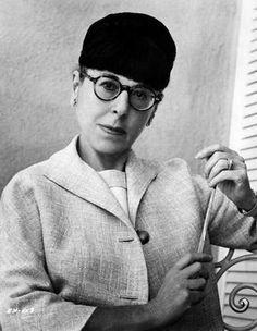Costume designer and 7 time Oscar winner Edith Head wearing a helmet hat.