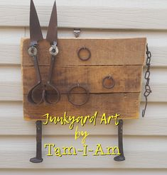Scrap metal art - cow made with pallet wood and old pair shears. Railroad spikes as feet