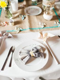 a bow tie + pinwheel at each place setting, photo by Rachel Havel http://ruffledblog.com/woodland-park-wedding #weddingideas #placesettings