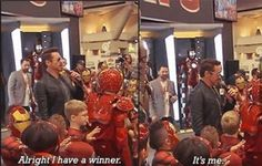 In a toy store, holding a iron man costume contest; Robert Downey Jr.