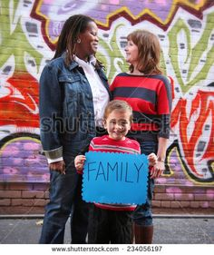 a cute family holding a sign that read family - Shutterstock Premier