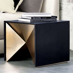 "Nova Side Table / Metal and leather merge on this origami-like form. In a tactile and graphic juxtaposition of materials, supple black leather frames a faceted brass-plated metal base. Though it appears simple, the design is quite complex. Kravitz Design observes that the unexpected geometric form unfolds ""an element of reveal. From one side, it's a tailored table...then you spin it around, and it unveils itself to you."""