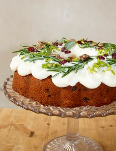Christmas bundt cake topped with sage leaves, rosemary sprigs, pistachio slivers, dried cranberries, pecans and edible gold lustre