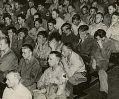 The image shows the faces of German POWs, captured by Americans, watching a film about a concentration camp. Their reaction were shame, fear and indifferent.