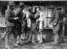 Soldiers preparing for World War I are given a regulation shave.