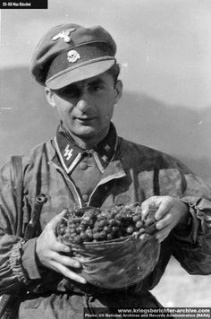 An SS soldier enjoys some grapes.