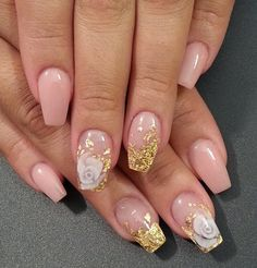 Nude and gold nail art design. Based with nude nail polish, the nails are then sprinkled with gold nail polish up to the tips and topped with flower embellishments.