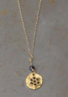 Pendentif médaille étoile en or ciselé 22 carats serti de diamants noirs par Esther Assouline pour l'Atelier des Bijoux Créateurs.