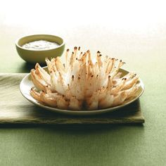 Blooming Onions Recipe from Taste of Home -- Instead of being battered and deep-fried, this onion is brushed with melted butter and mustard, sprinkled with bread crumbs and seasonings and baked. -- Shared by Kendra Doss of Kansas City, Missouri