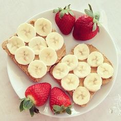 Toast with peanut butter, bananas on top & strawberries on the side