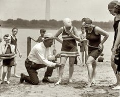 June 30, 1922. Washington policeman measuring the distance between knee and suit at the Tidal Basin bathing beach. Swimsuits were not to be over 6 inches above the knee!