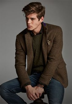 Man layers brown herringbone blazer over green cable-knit sweater
