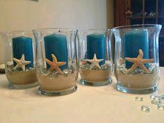 Centros de mesas con velas, arena y estrellas de mar