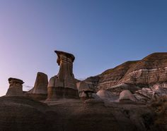 """Hoodoo! _ Just south of Drumheller Alberta we discovered the Hoodoo Trail. These are sandstone stacks which have eroded to form this distinctive shape over many years. These are also known as """"fairy chimneys"""" and if you've seen our photos from Cappadocia Turkey then this will look strangely familiar. _ Made it here just in time for sunset. After soaking up the view for half an hour we heard a distant coyote howl at the bright moon. Spectacular! _ #explorealberta @travelalberta #hoodoo"""