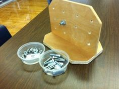 Put bolts through holes and twist nut on other side - great for fine motor skills! Love the upright board.