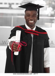 man in graduation cap and gown holding diploma Image by Wavebreak Media