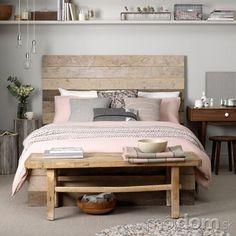 Un'altra soluzione con un utilizzo del legno originale con la struttura del letto e i comodini creati con legno, probabilmente di recupero. Le tonalità del grigio e del rosa danno un tocco romantico azzeccato.