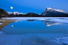 A clear winter night with a full moon rising up over the Fairholme Range and Mount Rundle sheds reflections on the...