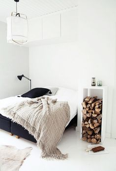 A white bedroom with a stack of logs in the nightstand... there's no doubt you'd stay warm in this space.