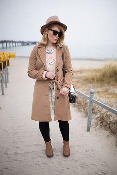 brauner mantel kombiniert mit weißem spitzenkleid und hut