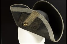 Royal Naval uniform, circa 1748. By the mid-18th century, the hat was generally carried under the arm to avoid the displacement of wigs and hair powder. This example of a three-cornered hat is of a type of felt called 'half-beaver' that was made by adding beaver hair to felt. The edges are bound in silver lace and the cockade is of black silk/cotton blend. The gold lace loop and button are of a later date. Hats were not mentioned in uniform regulations until 1795. National Maritime Museum