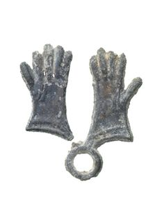 Pilgrim badge from the shrine of St Thomas Becket at Canterbury Cathedral. This badge is in the form of a pair of gloves that would have been linked by a loop at the cuffs (though now one of the gloves has snapped away). Various articles of Becket's clothing were worshipped at Canterbury, including his gloves, sandals, hair shirt, mitre, half-boots and girdle. Production Date: Late Medieval; late 14th century