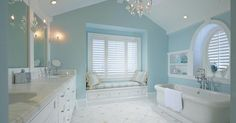 Blue and white bathroom with beadboard clad cathedral ceilings adorned with a glass chandelier ...