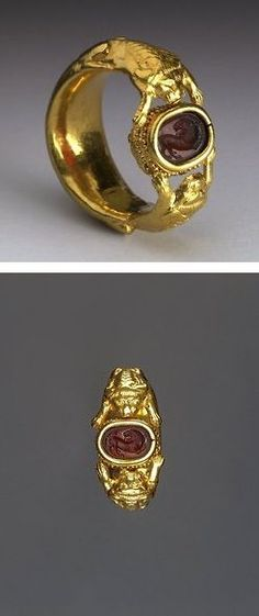 Etruscan. Gold Ring. 5th Century BC. This Gold finger-ring has two crouching lions on either side, the forepaws of which are outstretched and support a scarab in a gold band-setting. The engraved design depicts a lion with its head turned back. Gold work after A.D.: