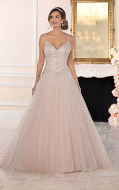 The epitome of glamour and elegance, this beaded tulle ballgown wedding dress from Stella York is ideal for the modern-day princess bride! Highlighted with a V-neckline and figure-flattering dropped waist, the bodice of this gown is adorned with beaded lace, with stunning beaded scallops around the neckline drawing attention to your face. A full, ballgown skirt is the statement-making feature of this style, giving a truly princess-worthy feeling with its sweet blush shade. The back of this…