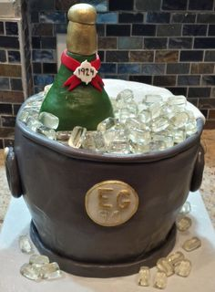 "Isn't this the most imaginative cake ever? Yes-- this is really a custom cake deigned for a special 90th birthday celebration. The champagne bottle is made out of fondant and the ice cubes are ""glacier"" mints. The chocolate cake is six layers deep with espresso buttercream and chocolate chips."