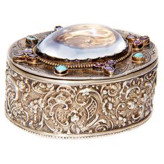 Antique Continental Gem set Snuff Box made of Sterling Silver with gold wash interior; top is set with a large moonstone and further set with turquoise and rhodolite garnets / Austria, 1900. Creator unknown.