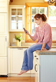 Mature woman using mobile phone in kitchen smiling