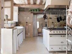 VERY French Kitchen - masonry cabinets, cabinet curtains, conveniently located pot & pan rack over a huge range, shuttered window, and bakers rack.