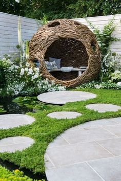 Woven Willow Bird Hide (Willow Sculpture) And Concrete Circular Slabs As A Path Over A Pond.