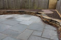 Grey Indian stone and dry stone wall curved with hand cut toppers #sheffield #landscaper www.rb-building.com